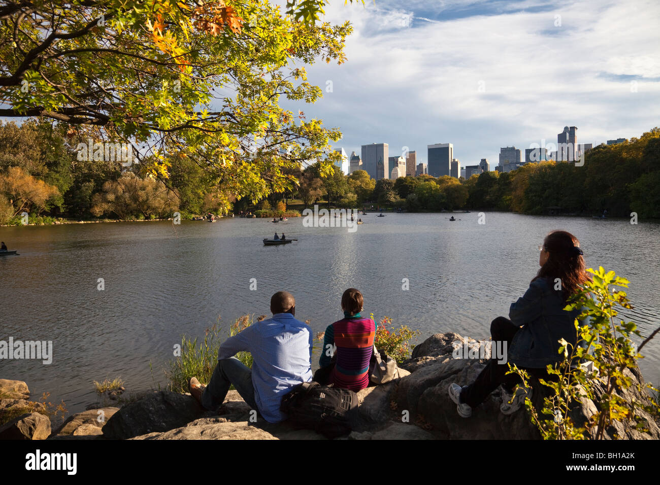 People watch boaters on The Lake in Central Park on a fall day with Manhattan skyline in distance. - Stock Image
