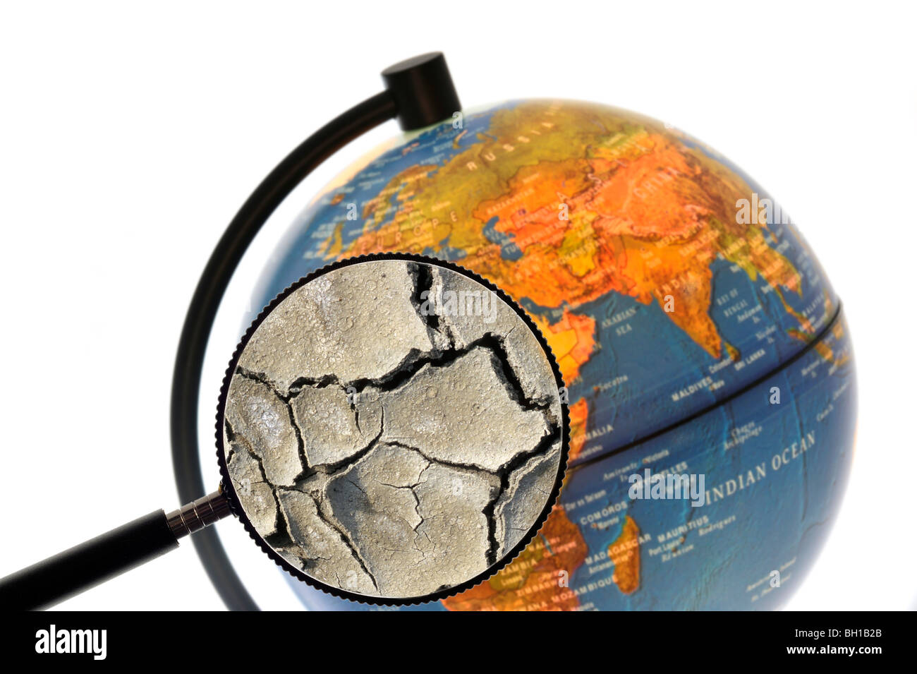 Cracked earth by drought seen through magnifying glass held against illuminated terrestrial globe - Stock Image
