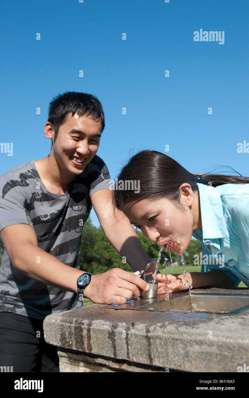 Young man assists young women at water fountain, Assiniboine Park, Winnipeg, Manitoba, Canada - Stock Image