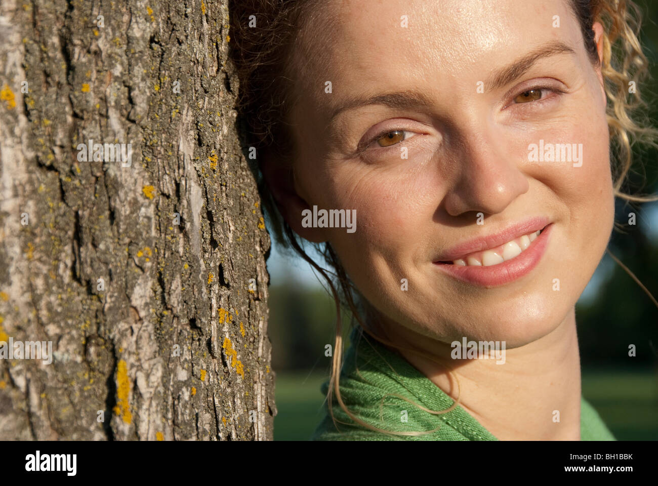 Head shot of woman in her 40s beside tree, Assiniboine Park, Winnipeg, Manitoba, Canada - Stock Image