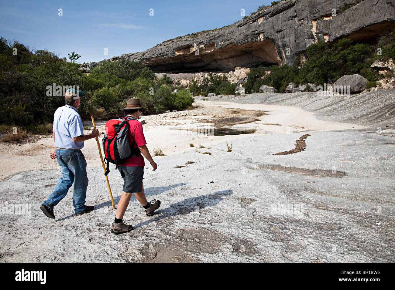Man and woman walking in dry river bed Seminole Canyon Texas USA Stock Photo