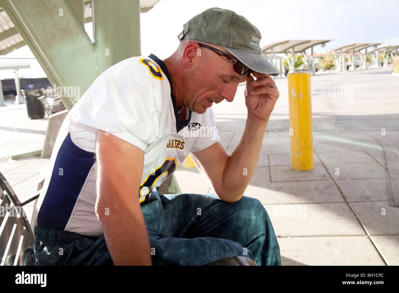 Distressed Man Waiting at Greyhound Bus Station - Stock Image