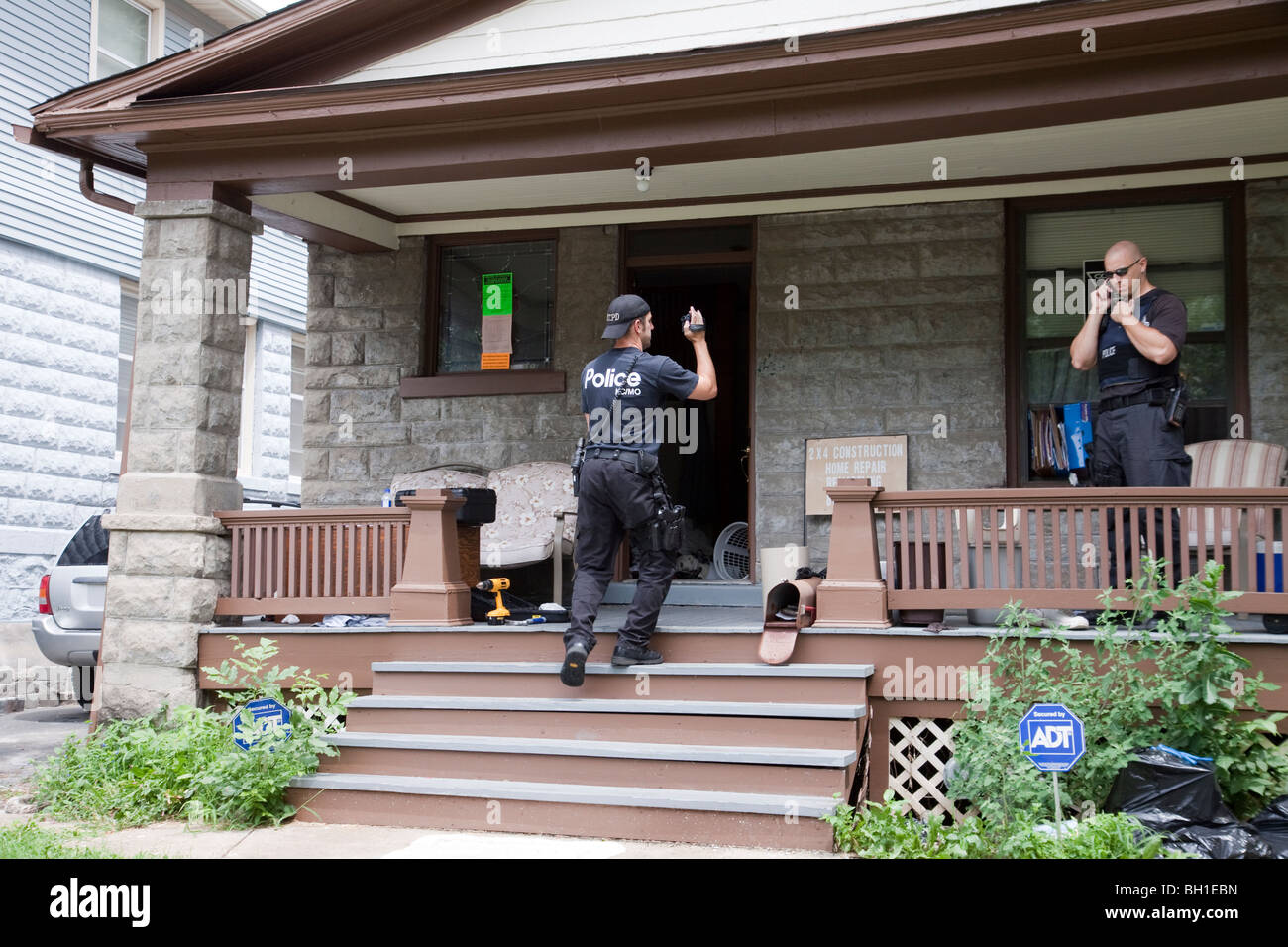 Police officer video-taping residence after search warrant. Done to document any damage caused by forced entry, - Stock Image