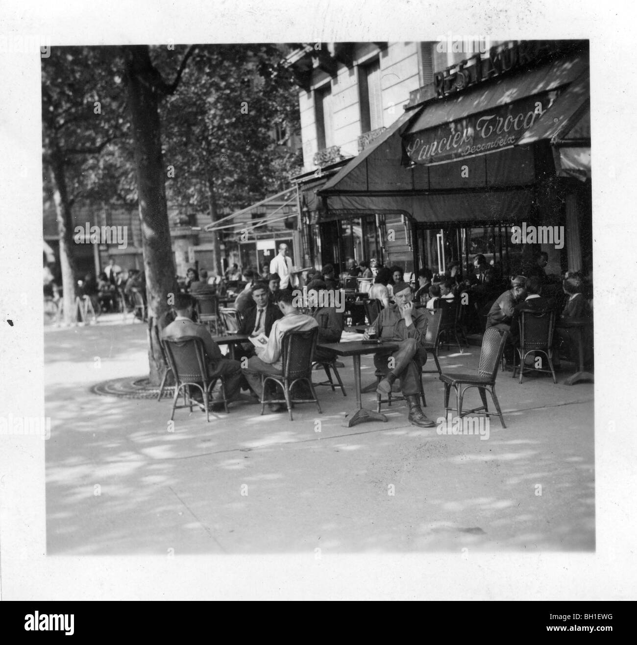Parisians and GIs seated at sidewalk cafe in liberated Paris, France at the conclusion of WWII. - Stock Image