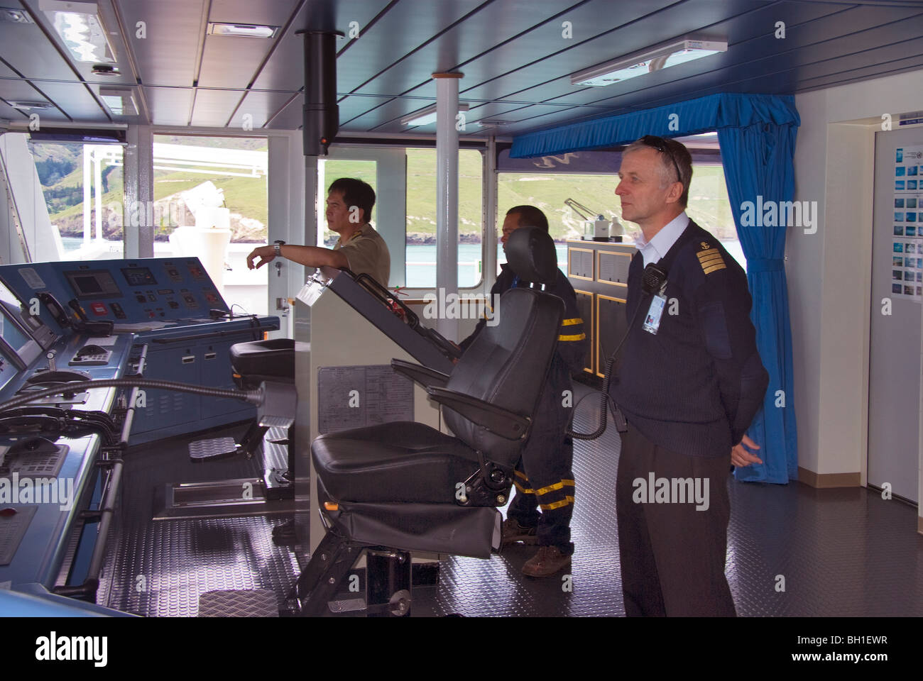 Captain and crew members on a ship's bridge as it approaches port - Stock Image
