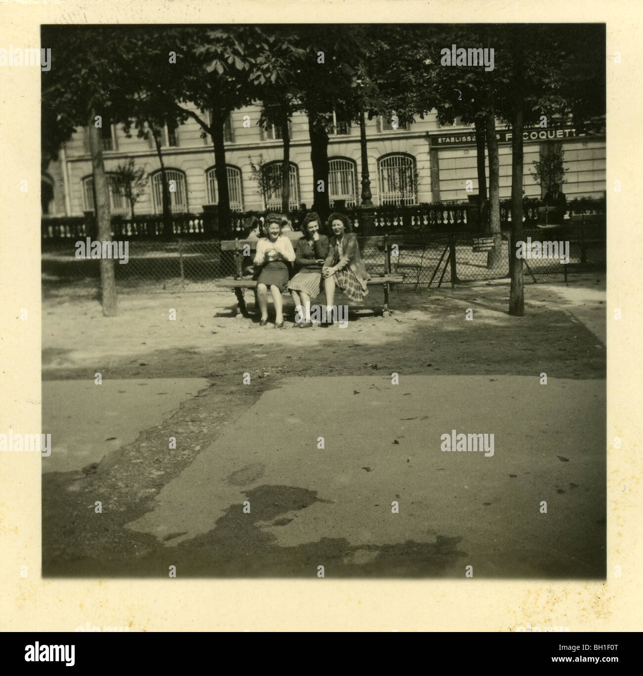 Trhee women relaxing on a park bench in liberated Paris, France at the conclusion of WWII. - Stock Image