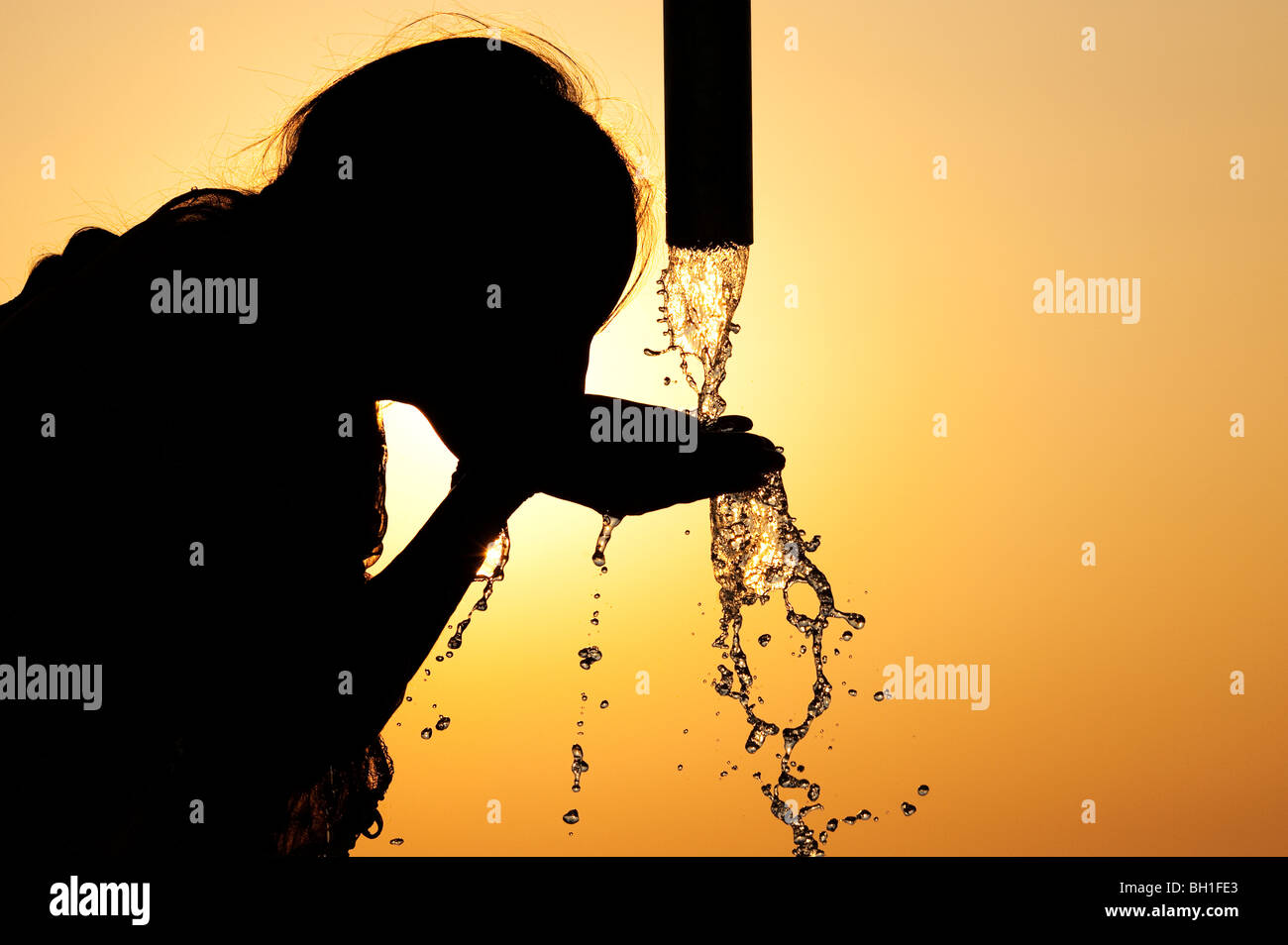 Silhouette of an Indian girl drinking from a water pump. India Stock Photo