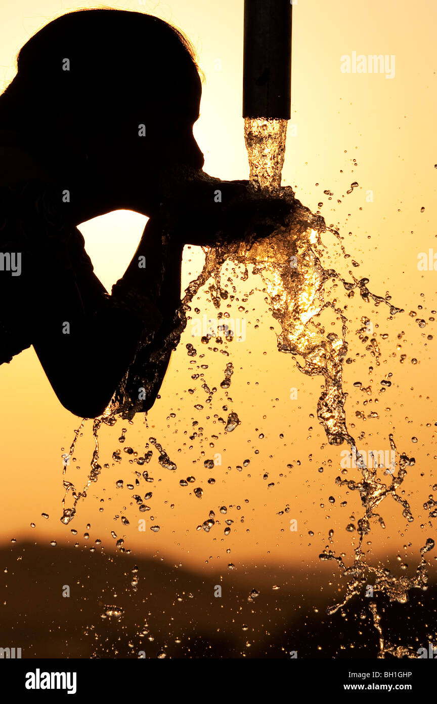Silhouette of an Indian girl drinking from a water pump. India - Stock Image