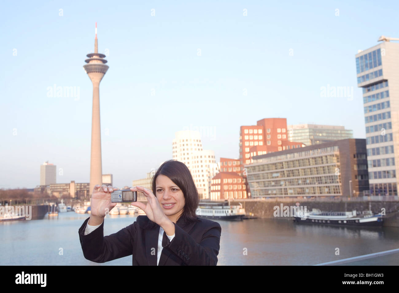 Young business woman making a selfportrait with mobile phone, in front of the city skyline, Media Harbour, Duesseldorf, - Stock Image