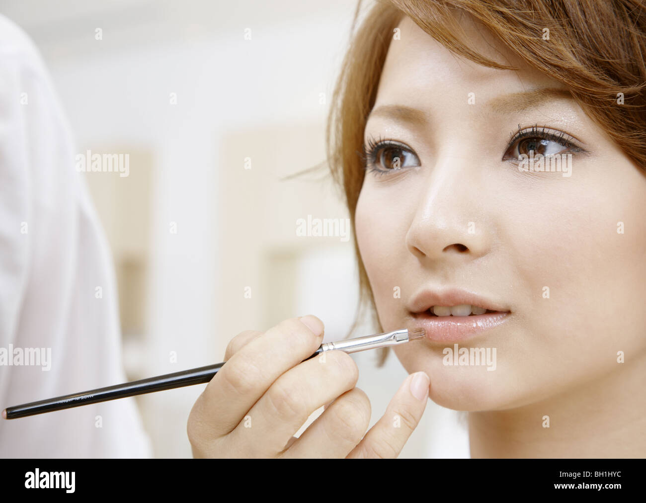 A young woman getting her makeup done - Stock Image