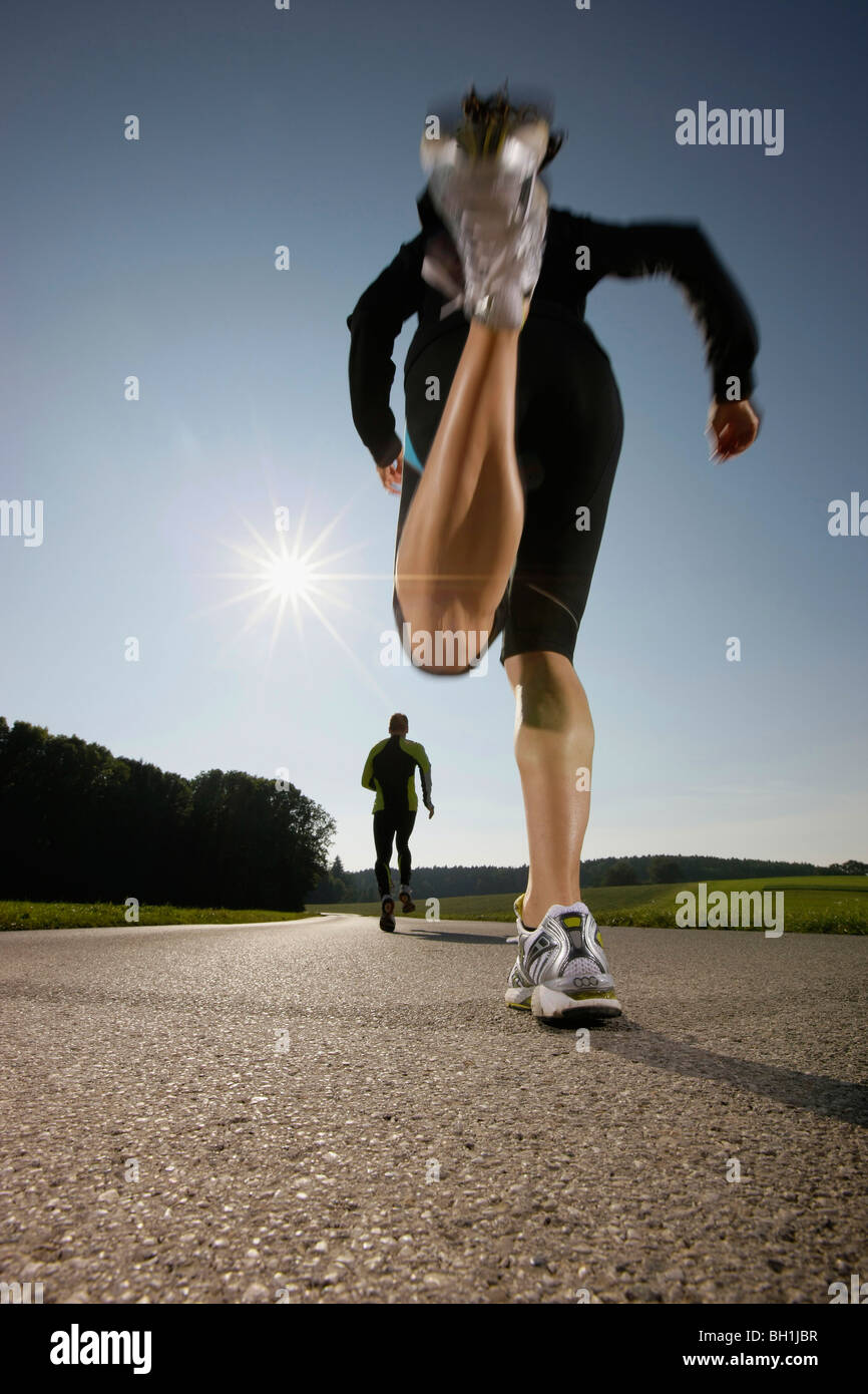 Two persons jogging along road, Strasslach-Dingharting, Bavaria, Germany - Stock Image