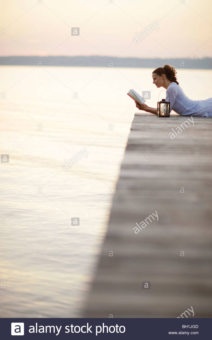 Woman lying on jetty at lake Starnberg while reading a book, Ambach, Bavaria, Germany - Stock Image