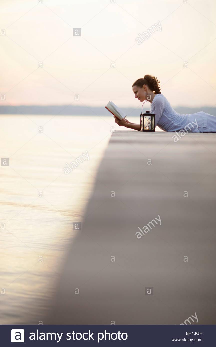 Woman lying on jetty at lake Starnberg while reading a book, Ambach, Bavaria, Germany Stock Photo
