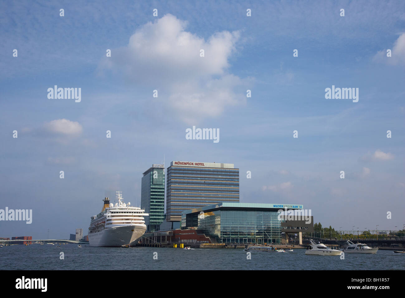 Cruise ship on the river Het Ij next to high rise buildings, Amsterdam, Netherlands, Europe - Stock Image