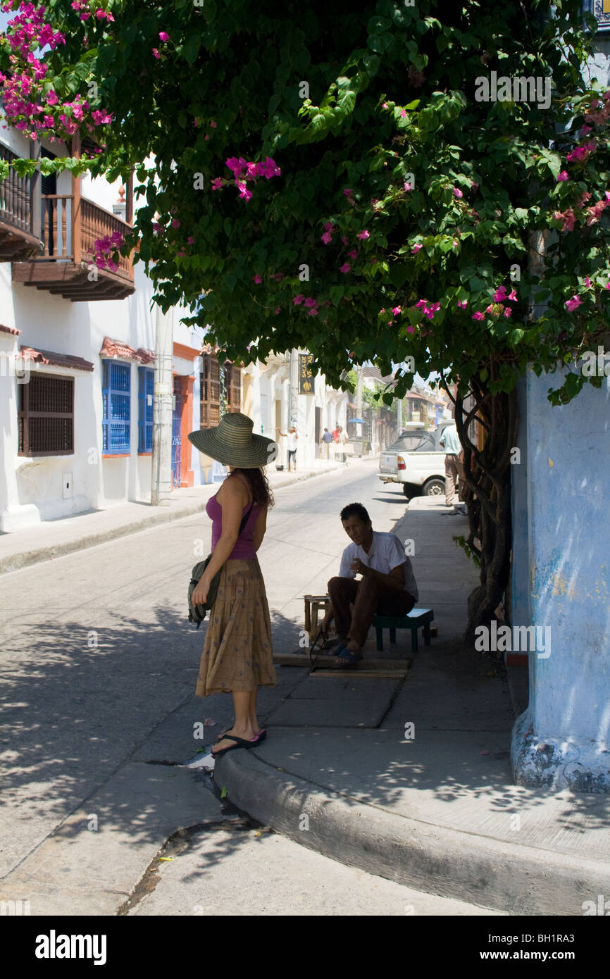 A tourist waits in shade to cross a quiet street in Cartagena's historic centre. Colombia. - Stock Image