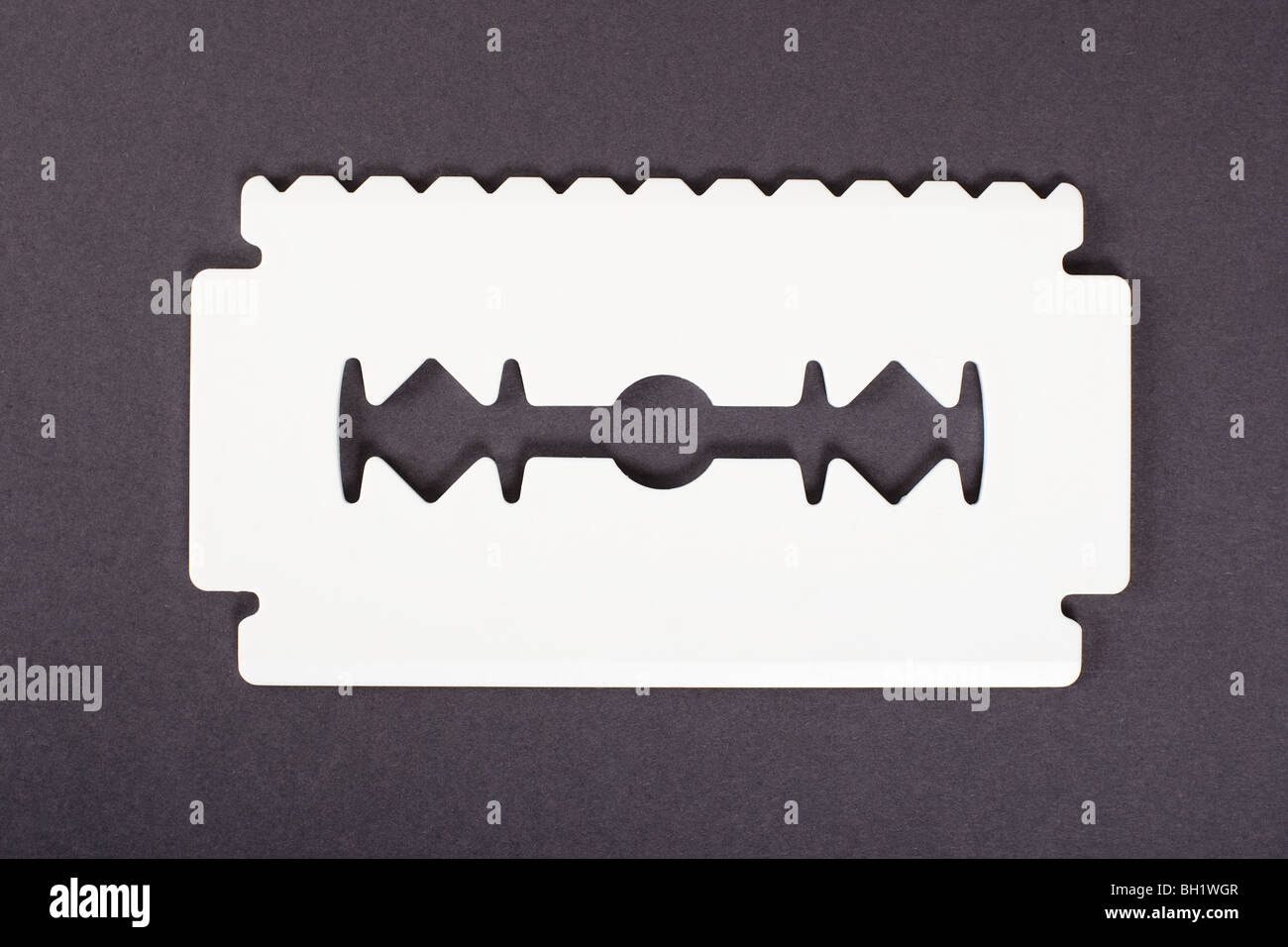 Big white ice scraper shaped as razor blade with one sharp edge and one toothed edge isolated on gray background. - Stock Image