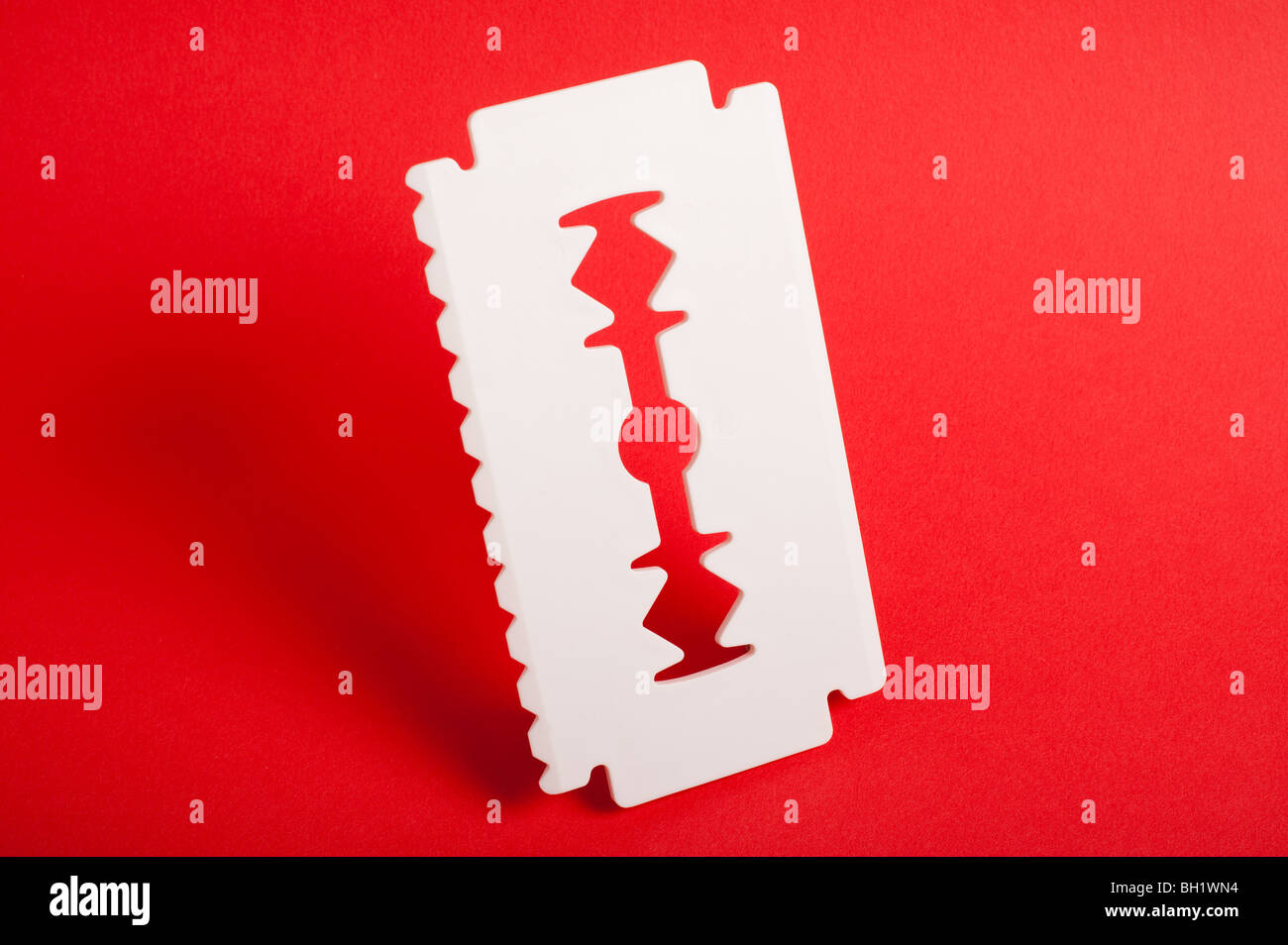 Big white ice scraper shaped as razor blade with smooth shadows. - Stock Image