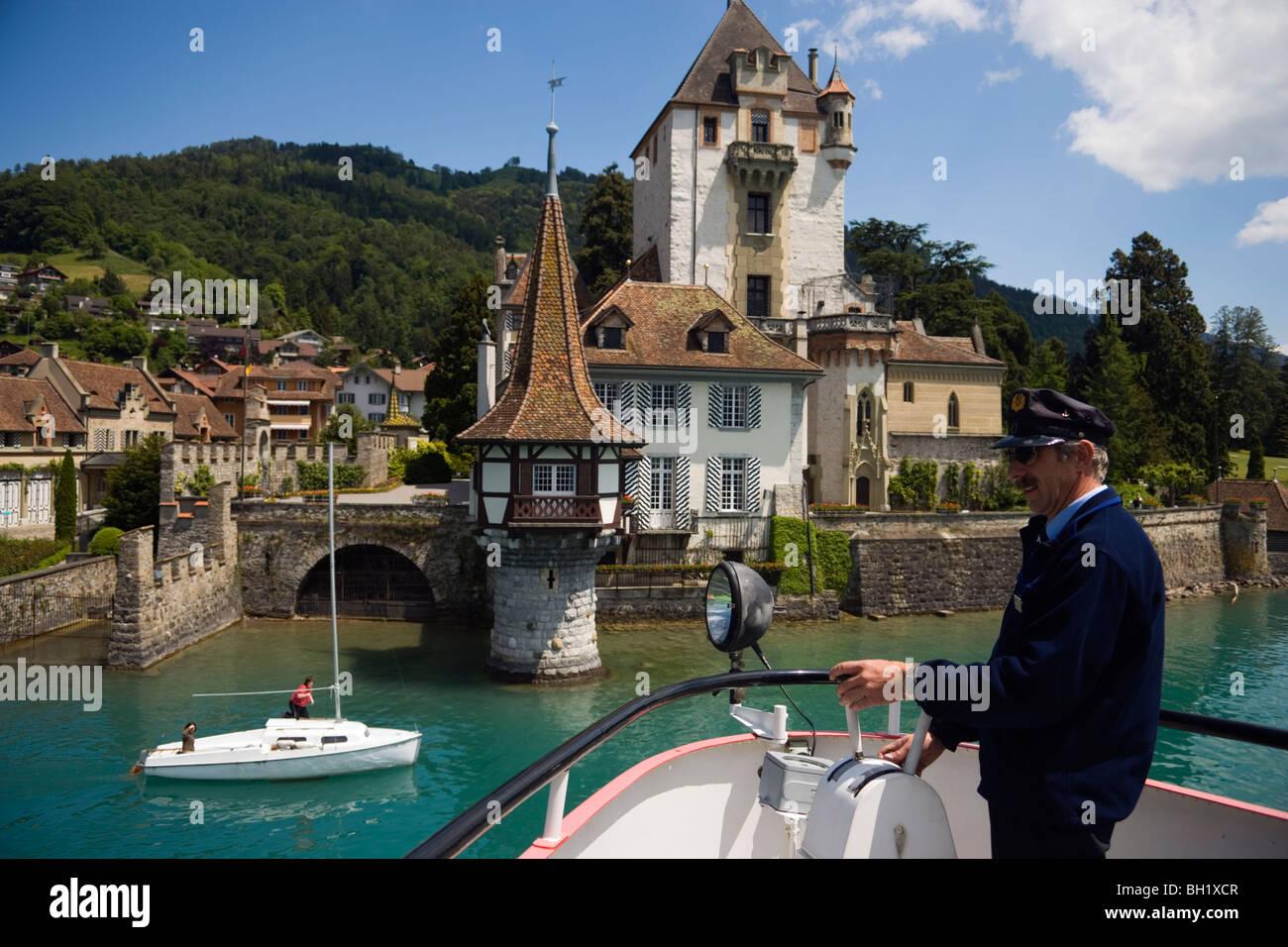 Captain during a docking manoeuvre, Sailing boat passing Castle Oberhofen, Lake Thun, Oberhofen, Bernese Oberland - Stock Image