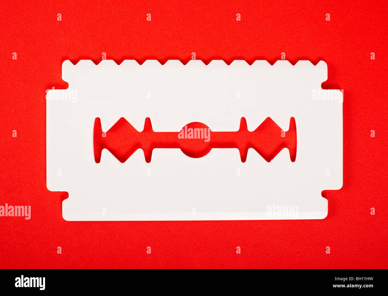 Big white ice scraper shaped as razor blade with one sharp edge and one toothed edge isolated on red background. - Stock Image