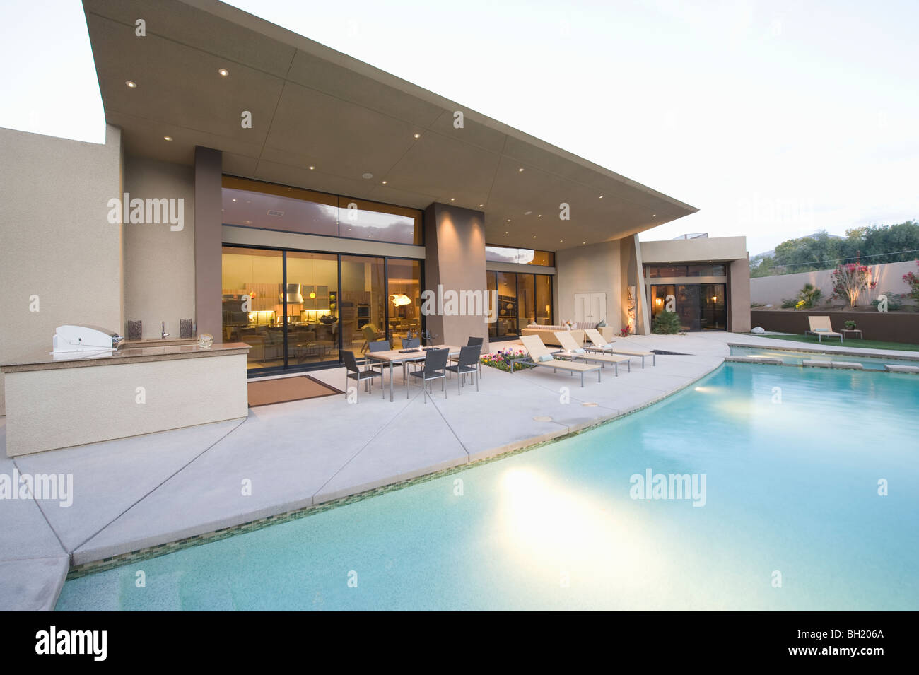 Swimming pool and paved seating area of Palm Springs home exterior - Stock Image