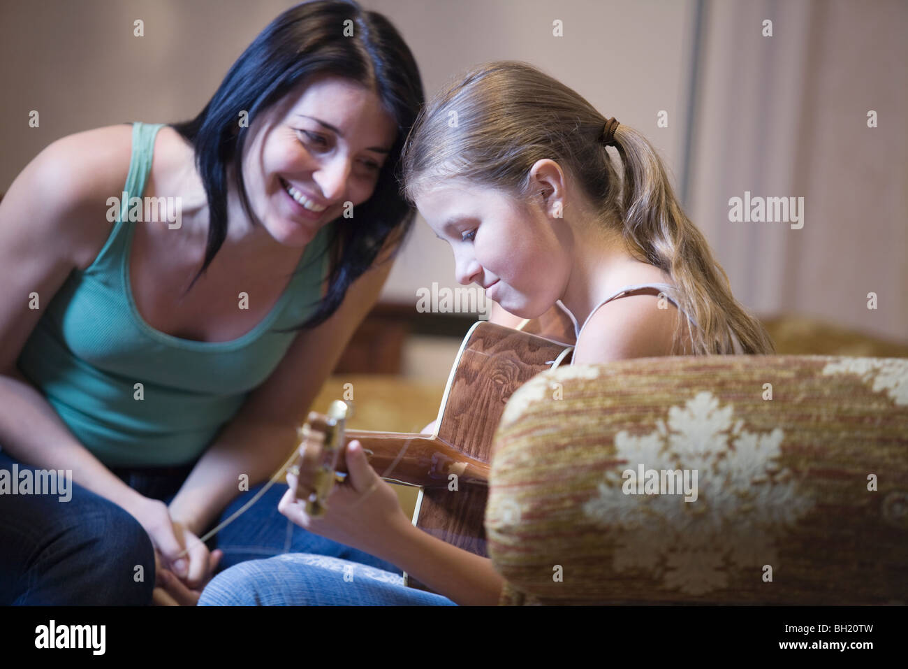 Women encourages young girl with the guitar - Stock Image