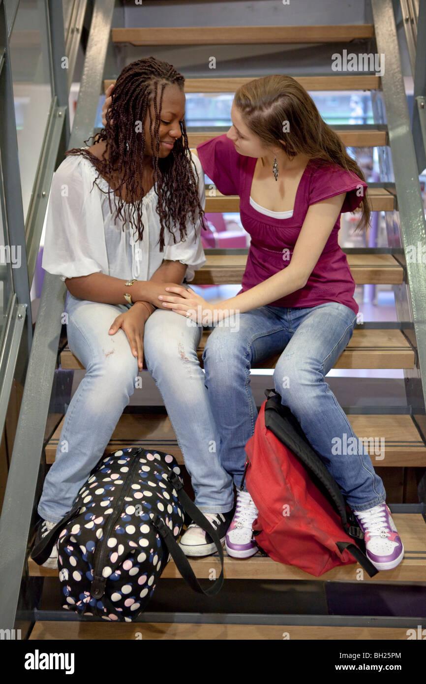 Teenage girl is comforting her friend - Stock Image