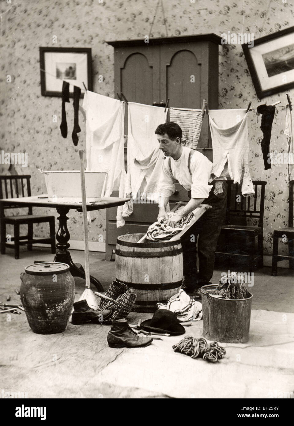 Pipe Smoking Bachelor Doing His Own Laundry - Stock Image