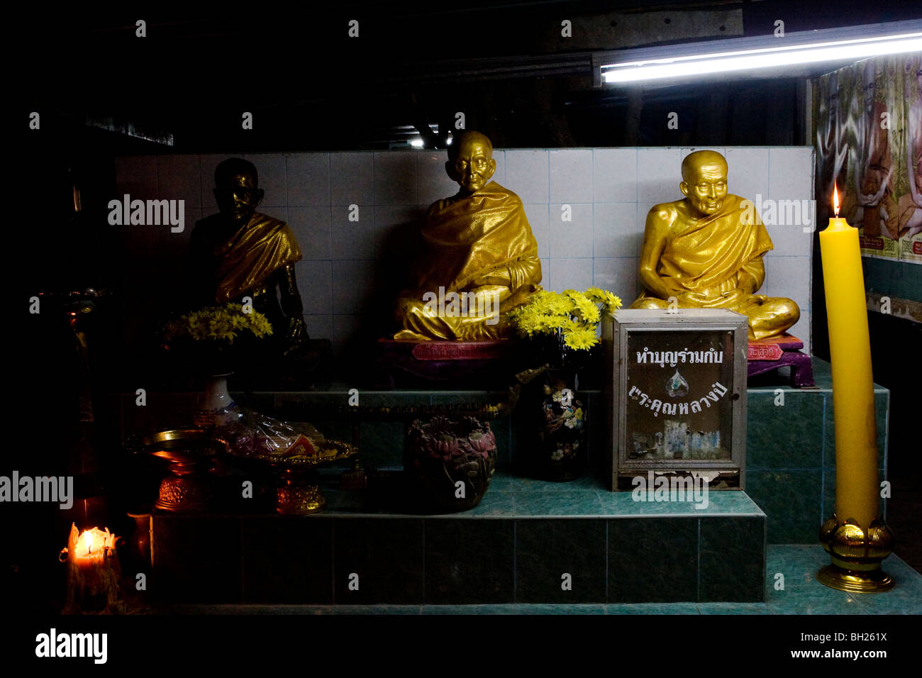 Statues of revered monks on a shrine at Wat Klang Si Chaloensuk, Thailand - Stock Image