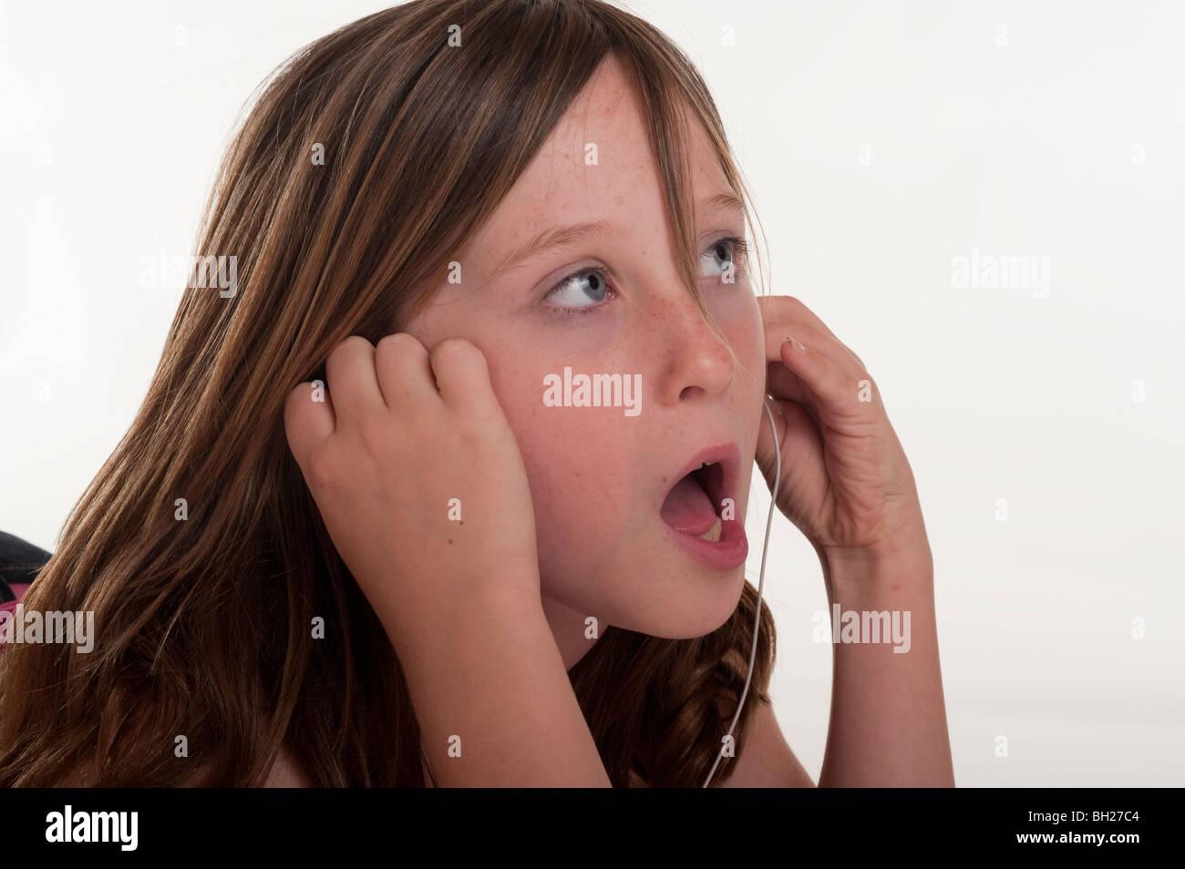 little girl listening to music through earphones - Stock Image