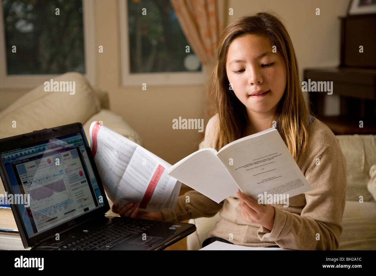 Korean/white young girl 11 years old, does financial research and investing online. - Stock Image