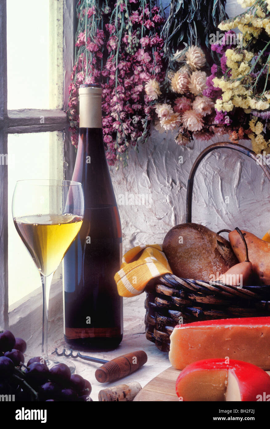 Wine bottle with glass in window - Stock Image