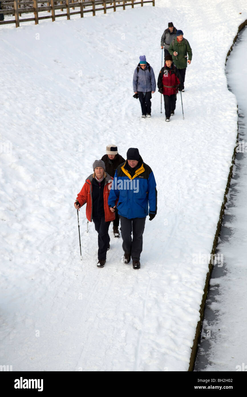 Group of walkers  out enjoying the snow along the Chesterfield canal towpath Derbyshire England - Stock Image