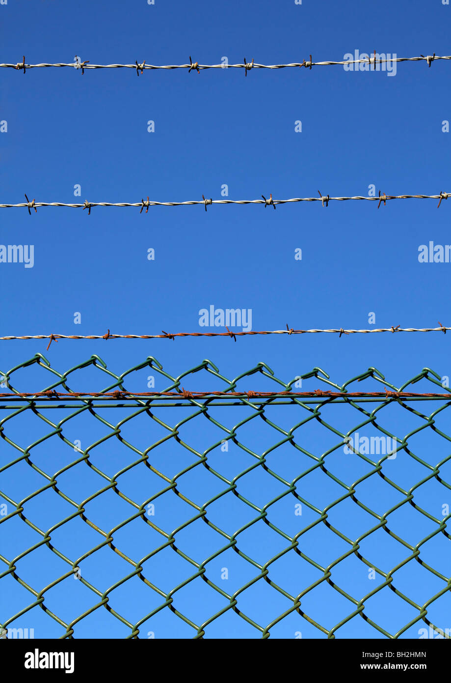Old barbed wire fence against blue sky - Stock Image