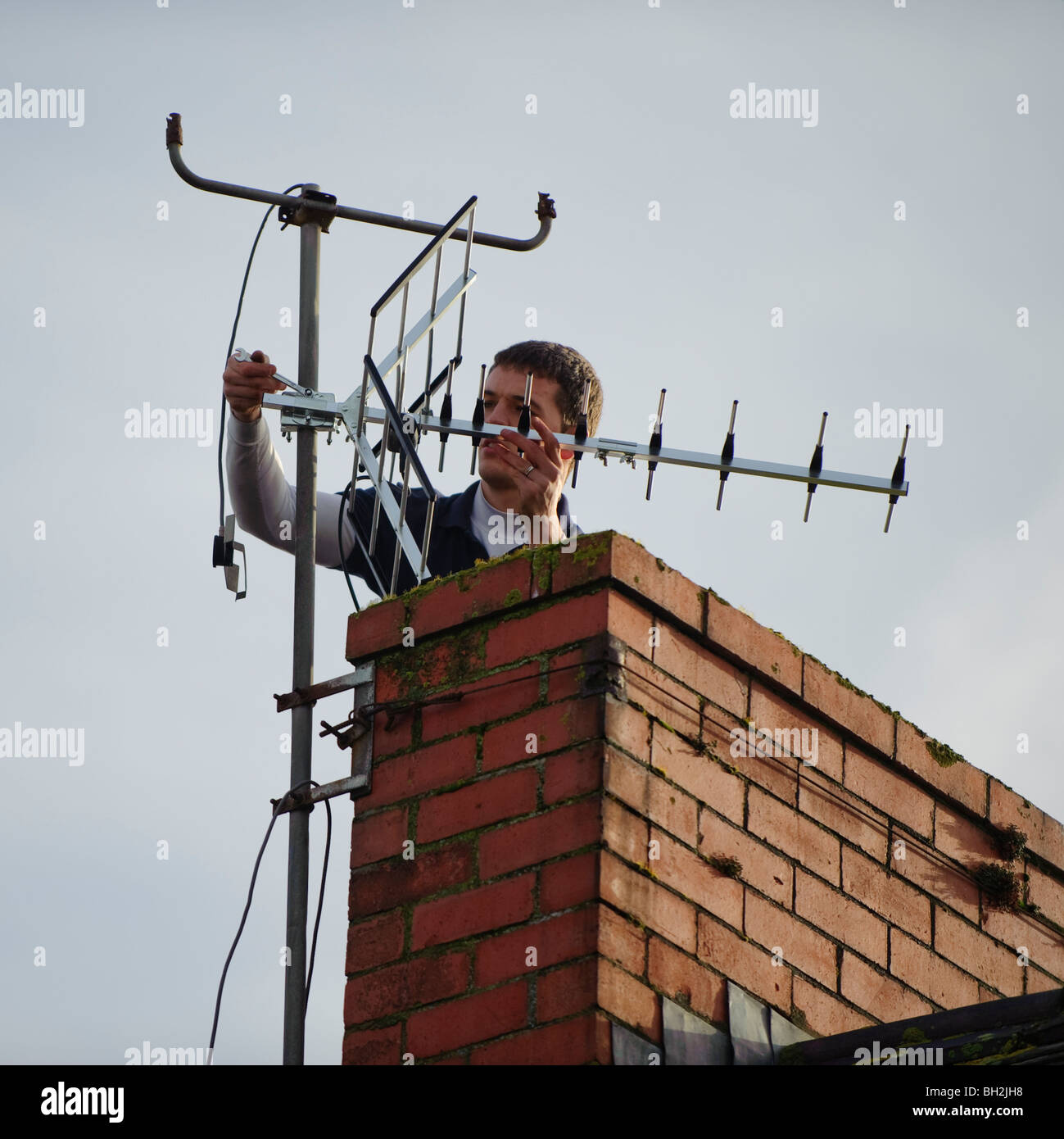 A television engineer installing new digital tv compatible aerial on to a chimney of a house - Stock Image