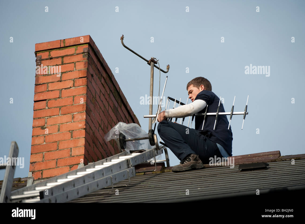 A young television engineer installing new digital tv compatible aerial on to a chimney of a house - Stock Image