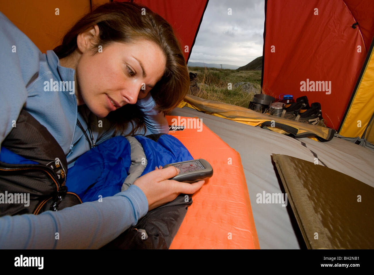 Female hiker in tent with GPS unit - Stock Image