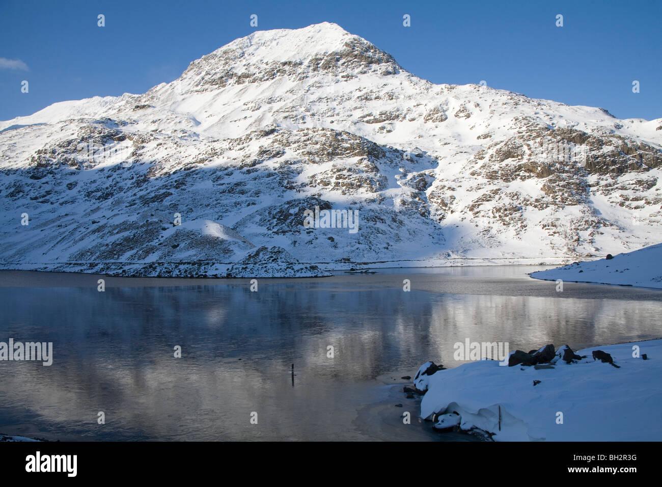 Gwynedd North Wales UK January Looking across Llyn Llydaw towards snow covered Crib Goch from Miners Track - Stock Image