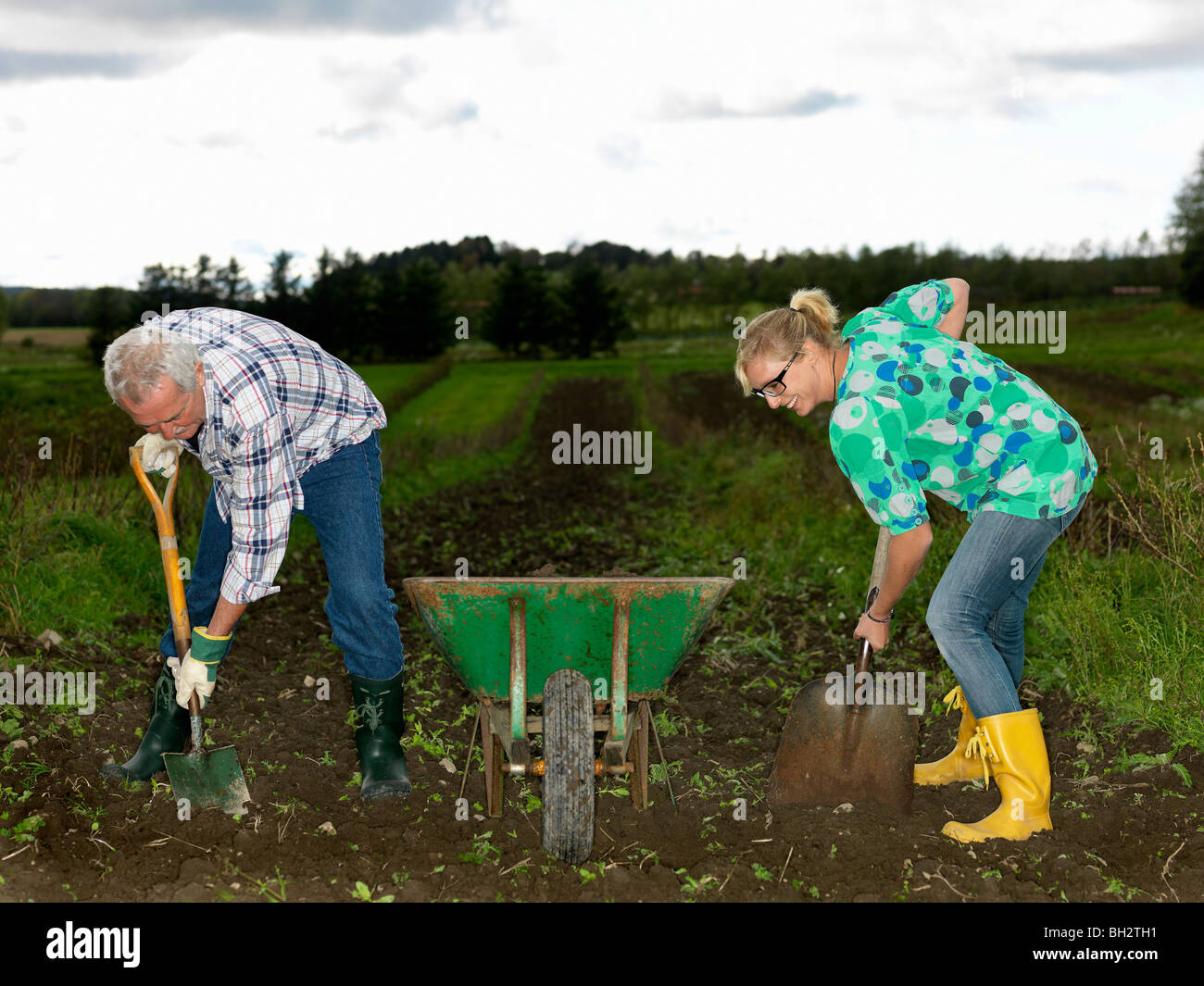 Man and woman shoveling dirt Stock Photo
