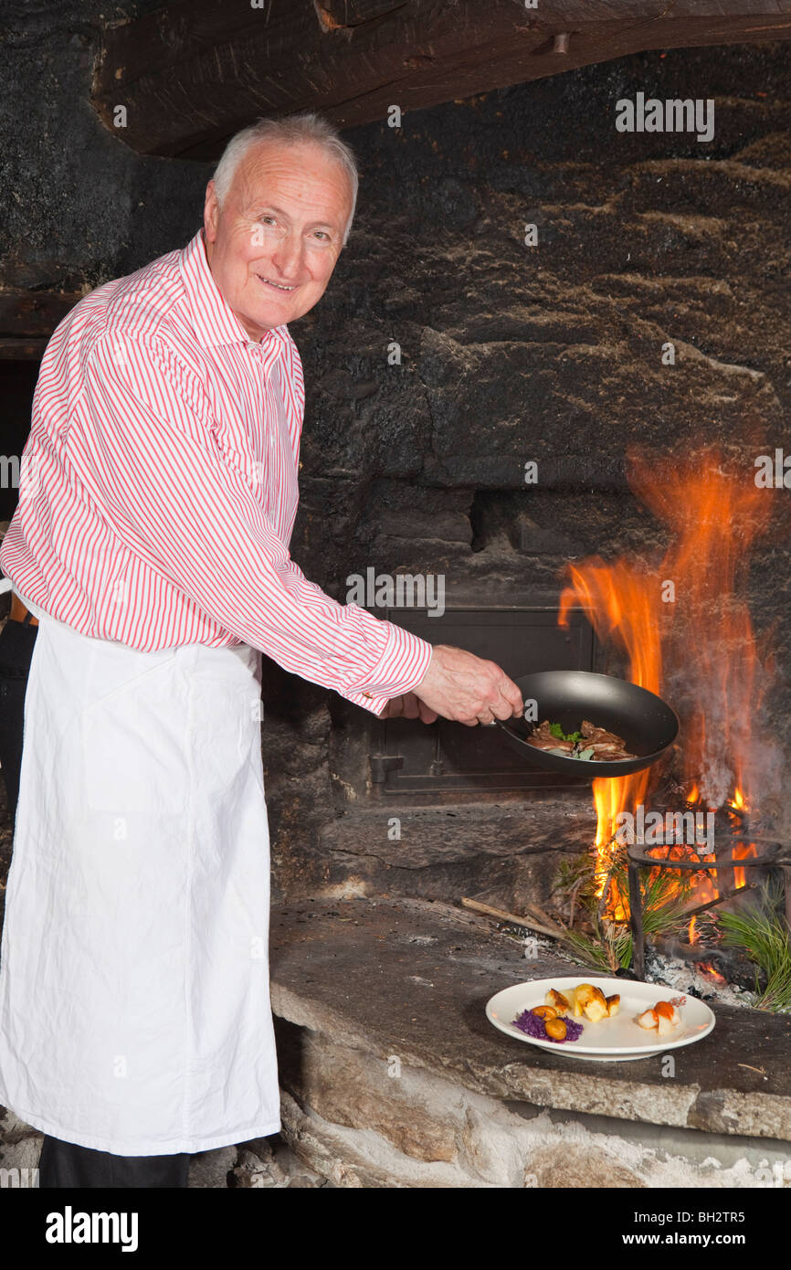 elderly cook by fireplace serving food - Stock Image