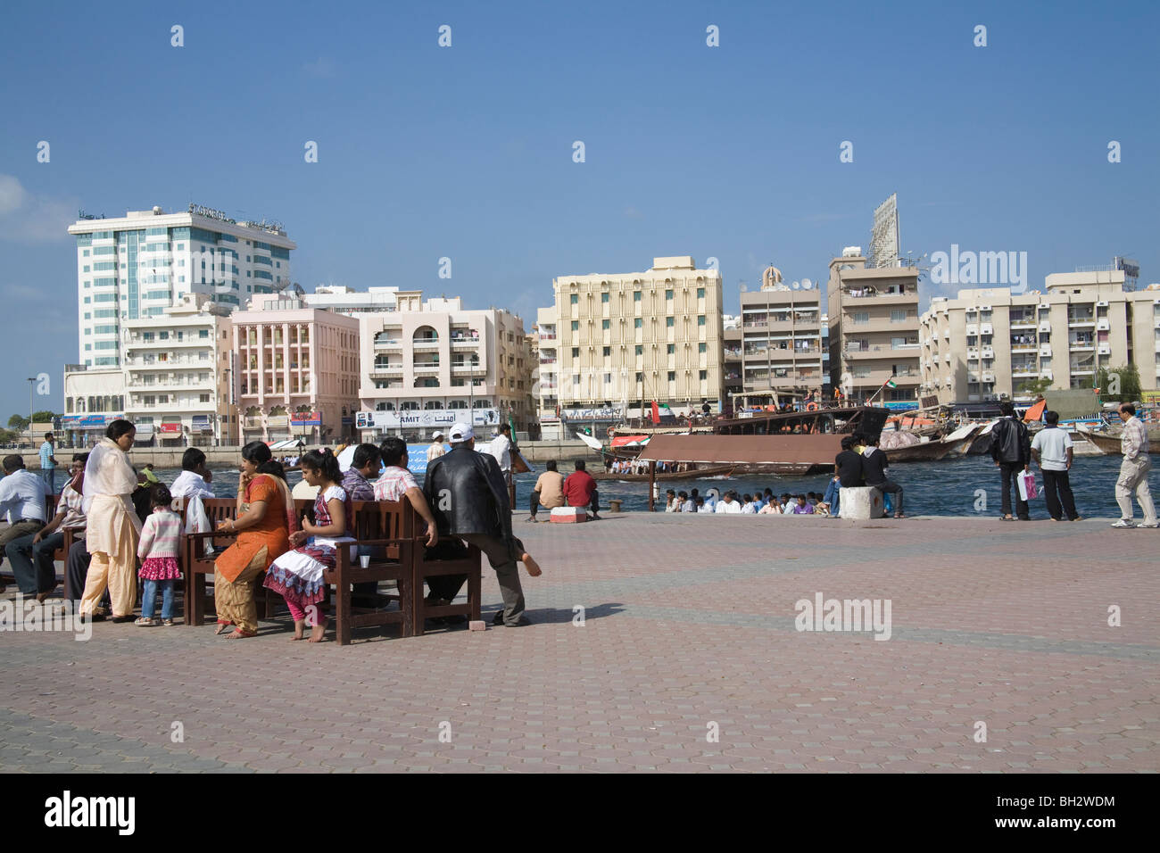 Dubai United Arab Emirates Group of Indians sitting outside in the sunshine on wooden benches with views across Stock Photo
