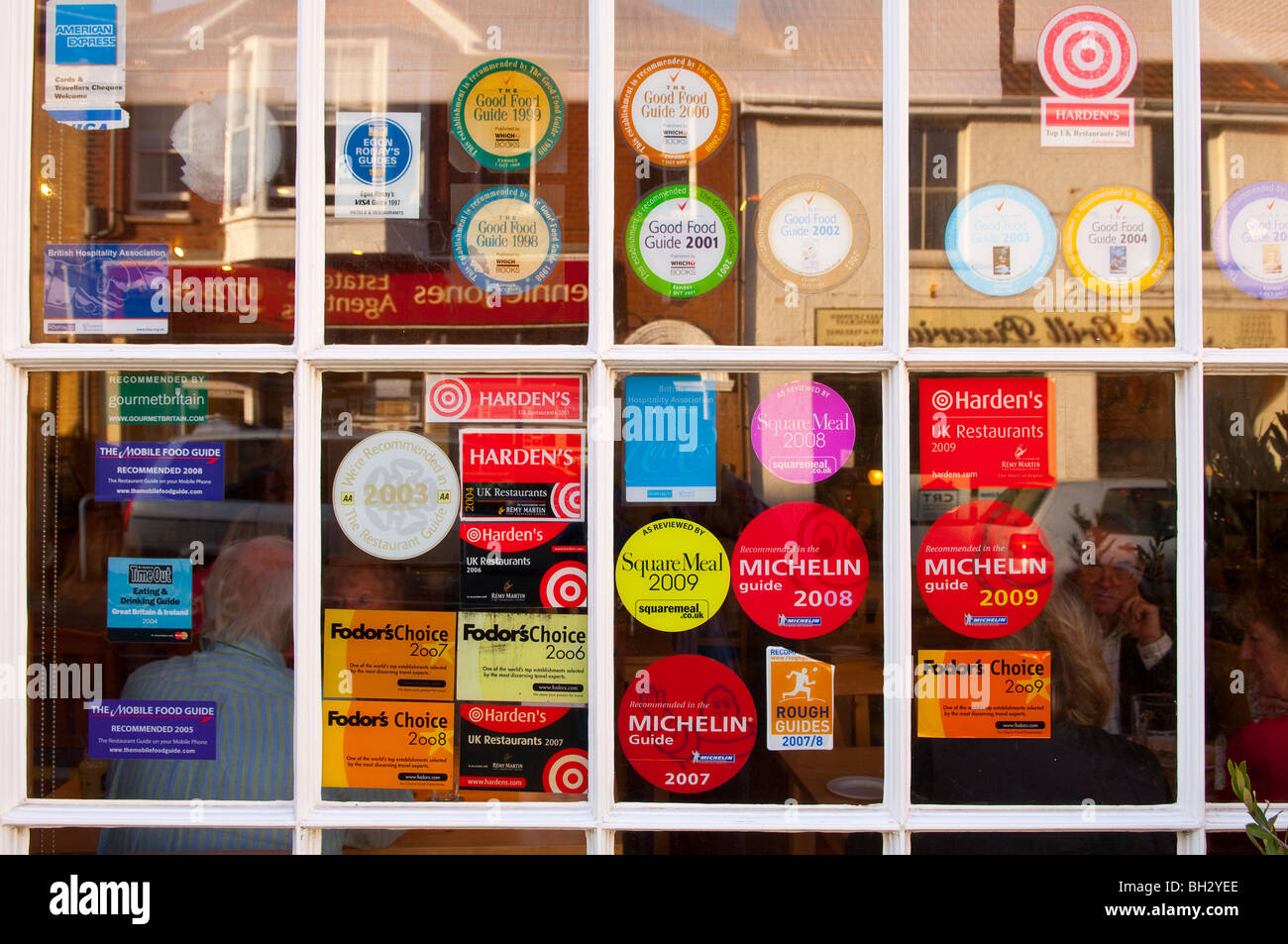 Stickers in a uk restaurant window which have been awarded in various guides stock image