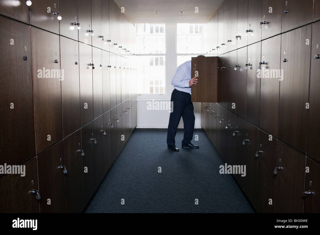 Businessman with head in locker - Stock Image