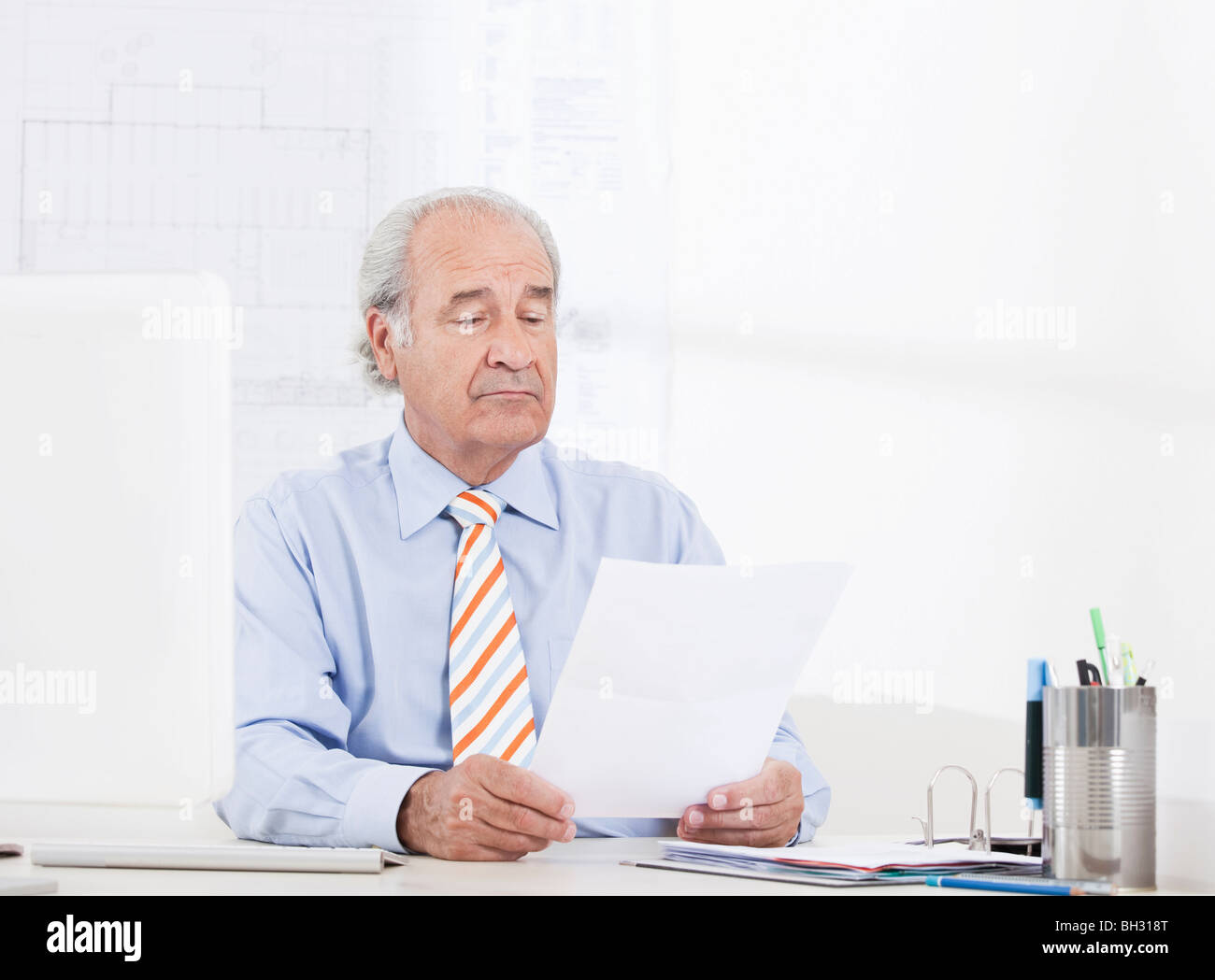 Man reading a paper in the office - Stock Image
