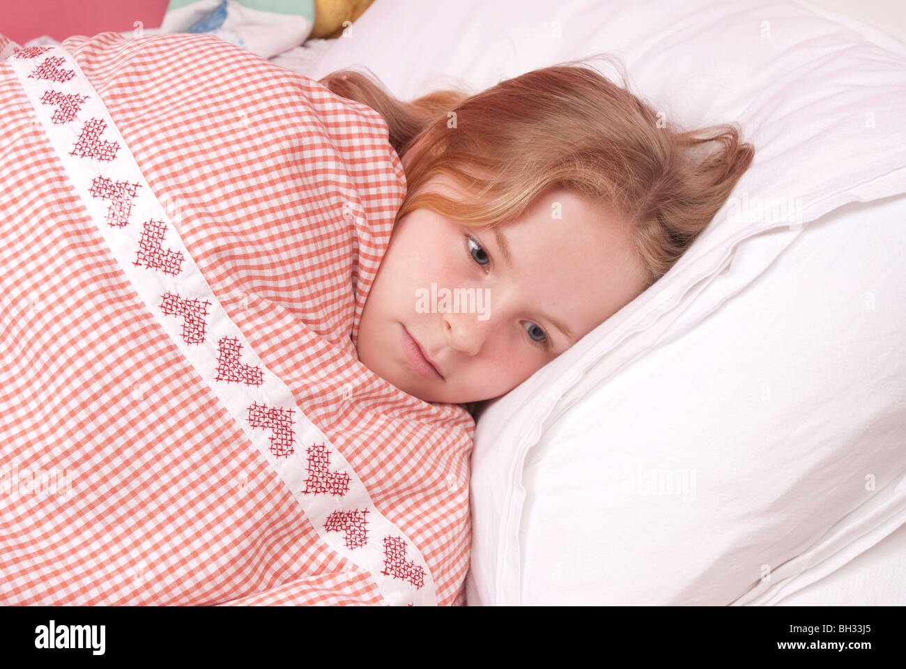 Young girl awakes in her bed at night UK Stock Photo