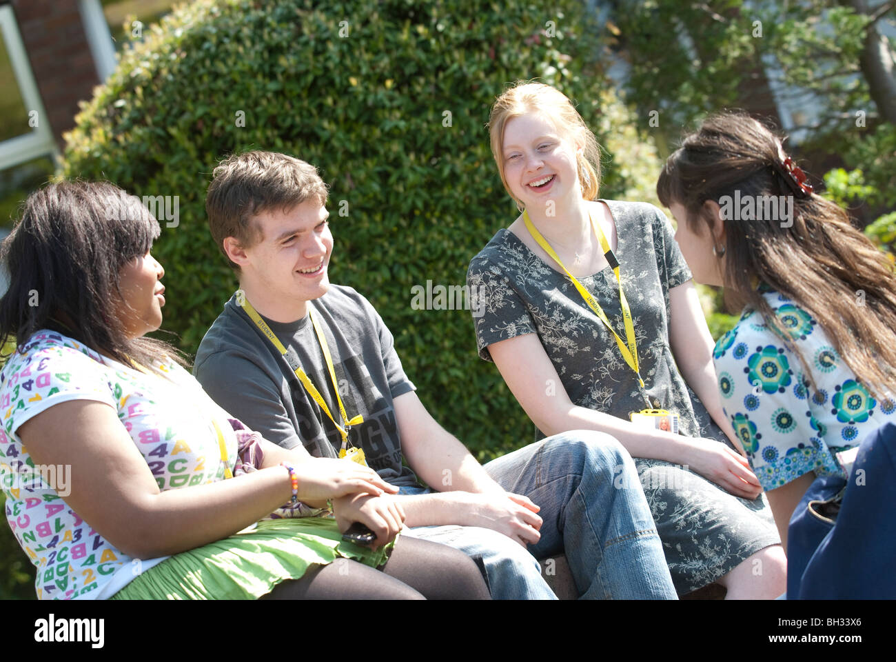 Pupils chill out in the sunshine at school UK - Stock Image
