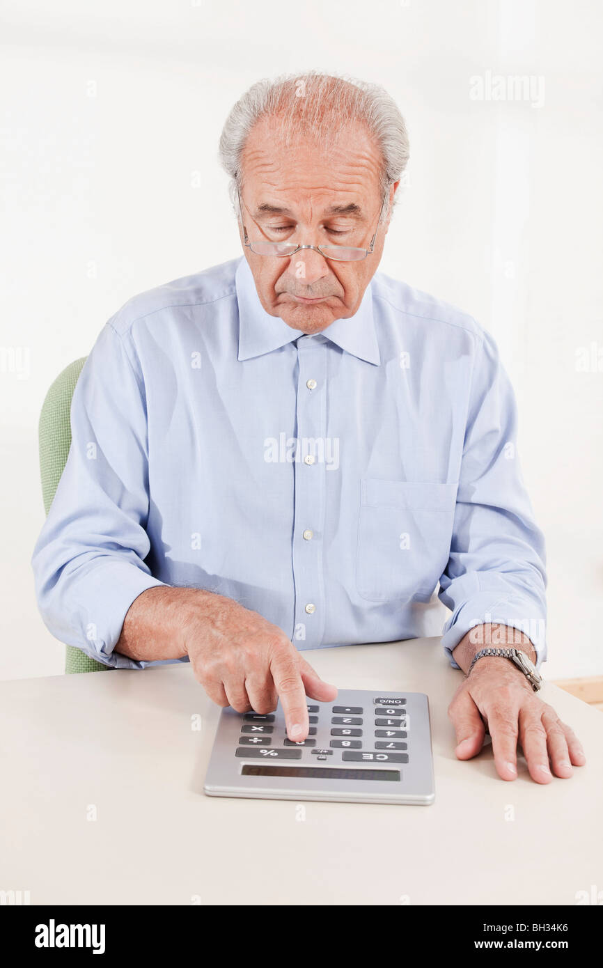 Senior typing on a huge calculator - Stock Image