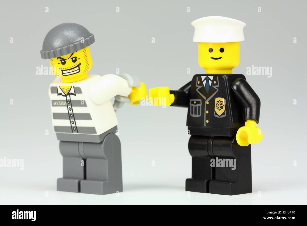 Lego policeman arresting a criminal - Stock Image