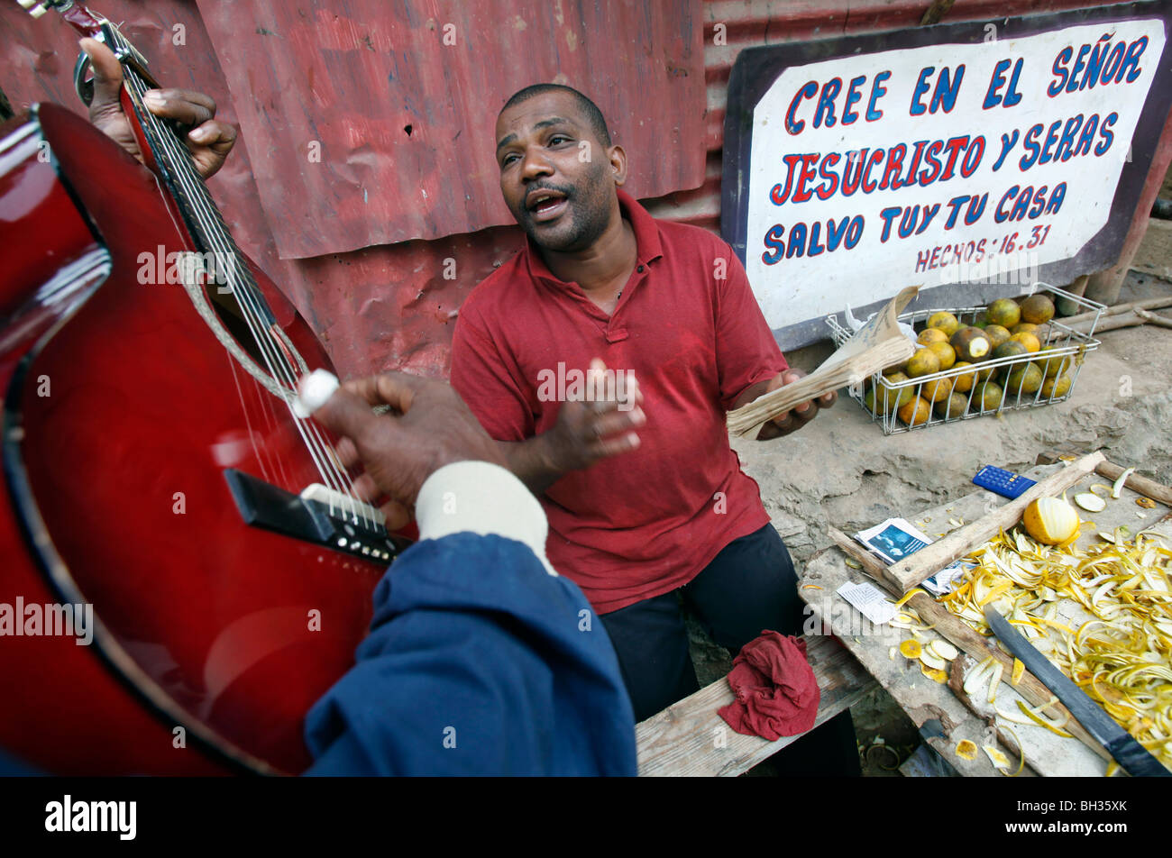 A man sings religious songs accompanied by a guitar at a roadside stand, Samana peninsula, Dominican Republic - Stock Image