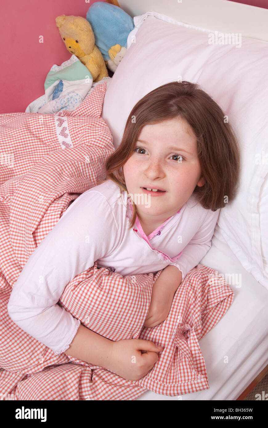 Young girl awakes in her bed at night UK - Stock Image