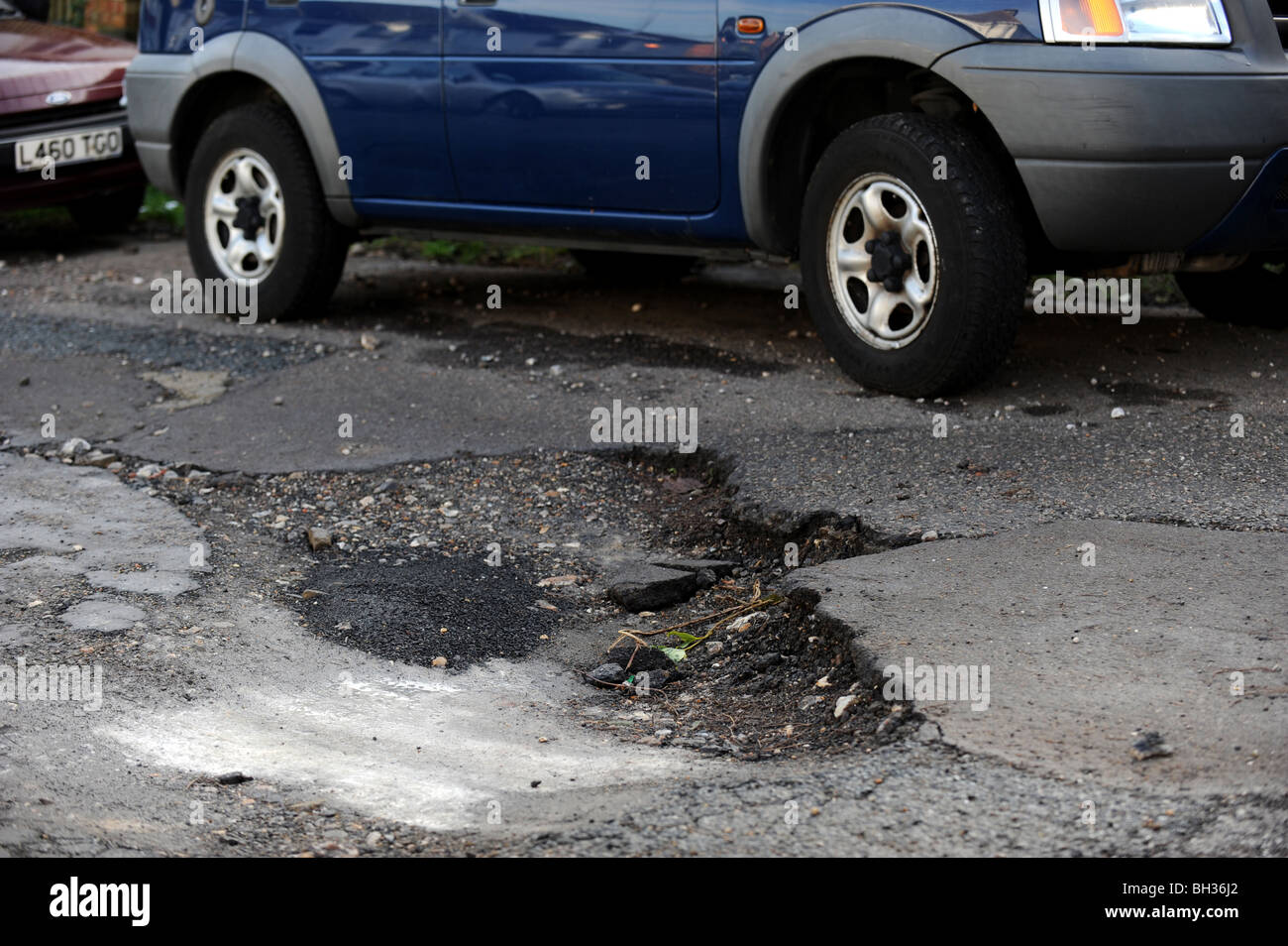 Potholes in a busy road caused by the recent snow and freezing weather - Stock Image